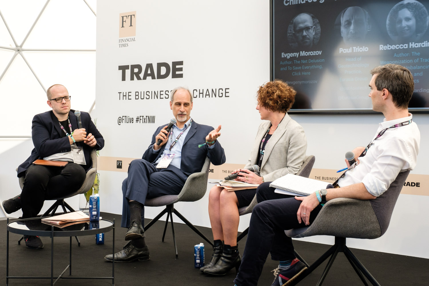 A photograph of a panel discussion at the Financial Times stage at the TNW event in Amsterdam. The photo shows Paul Triolo talking to Evgeny Morozov and Rebecca Harding.
