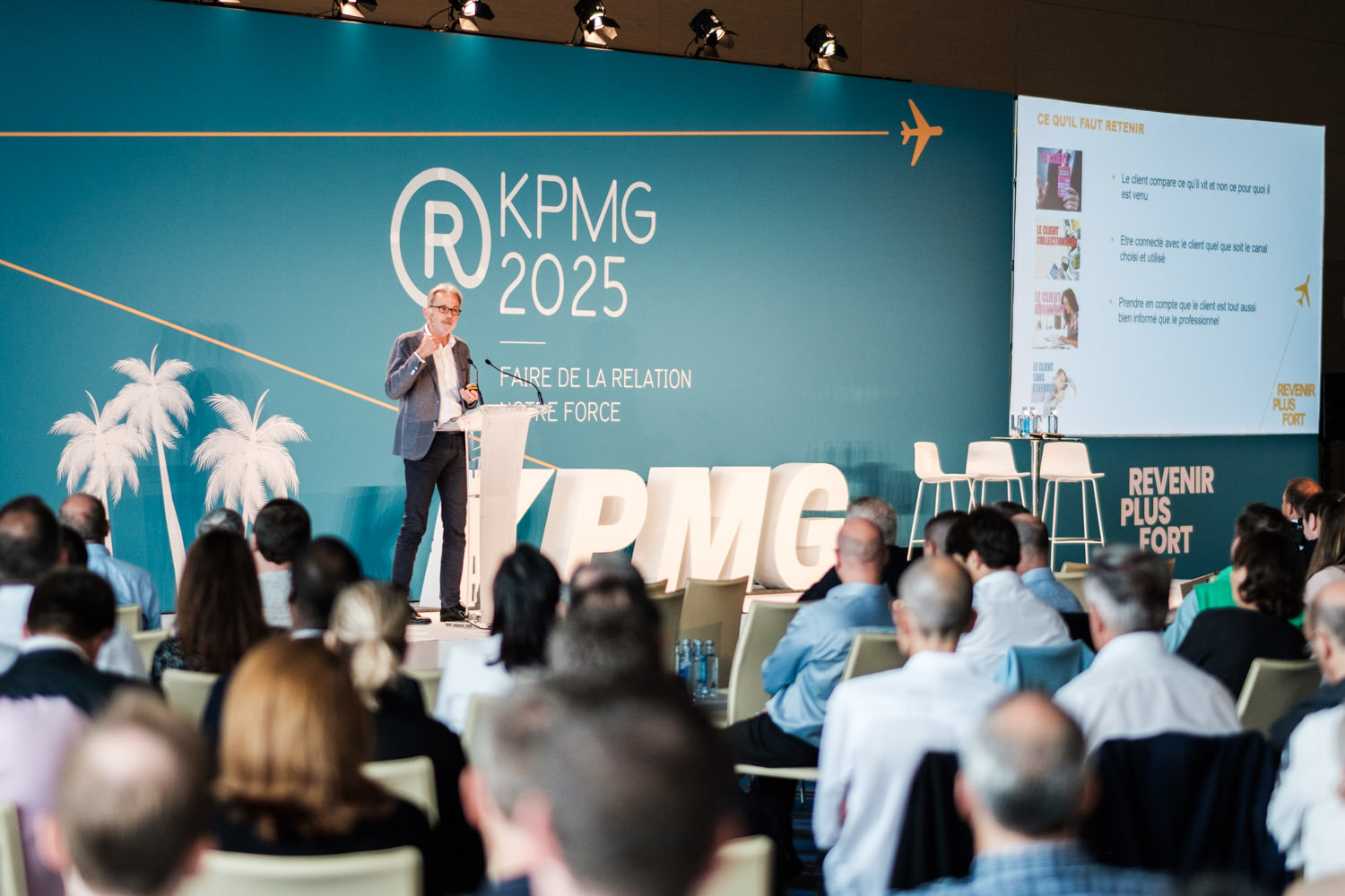 A photography of a man on stage speaking at the KPMG conference event at the W Hotel, in Barcelona, Spain.
