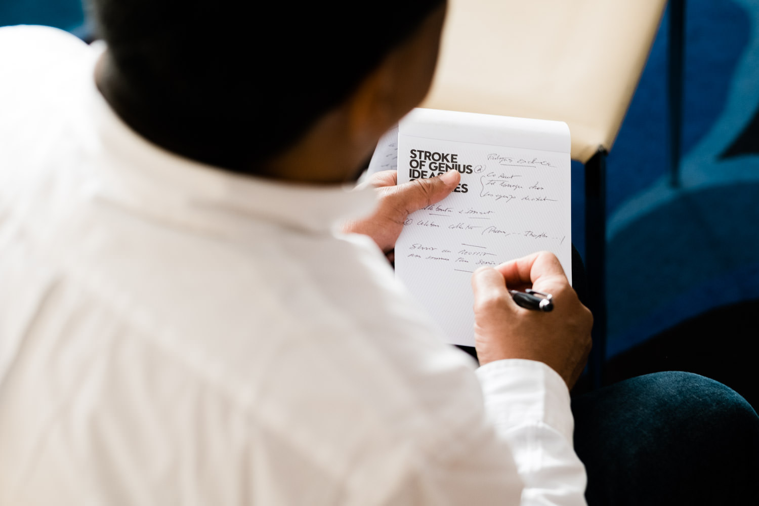 A photograph of a man taking notes in a notebook, during the KPMG conference at the W Hotel, in Barcelona, Spain