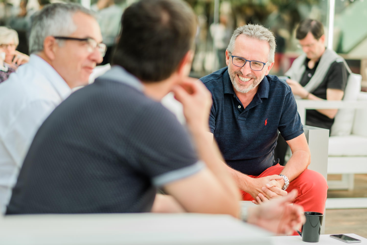 A photograph of 3 professional men, talking and smiling, at the KPMG event in the W Hotel, in Barcelona, Spain