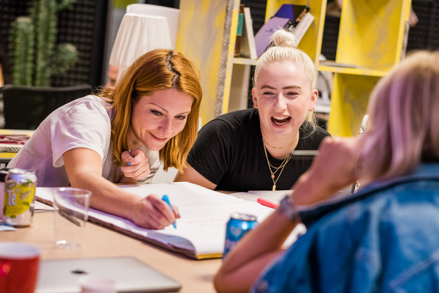 A photography of 2 young women laughing and having fun whilst participating in a workshop, during a team building event, in Barcelona, Spain.
