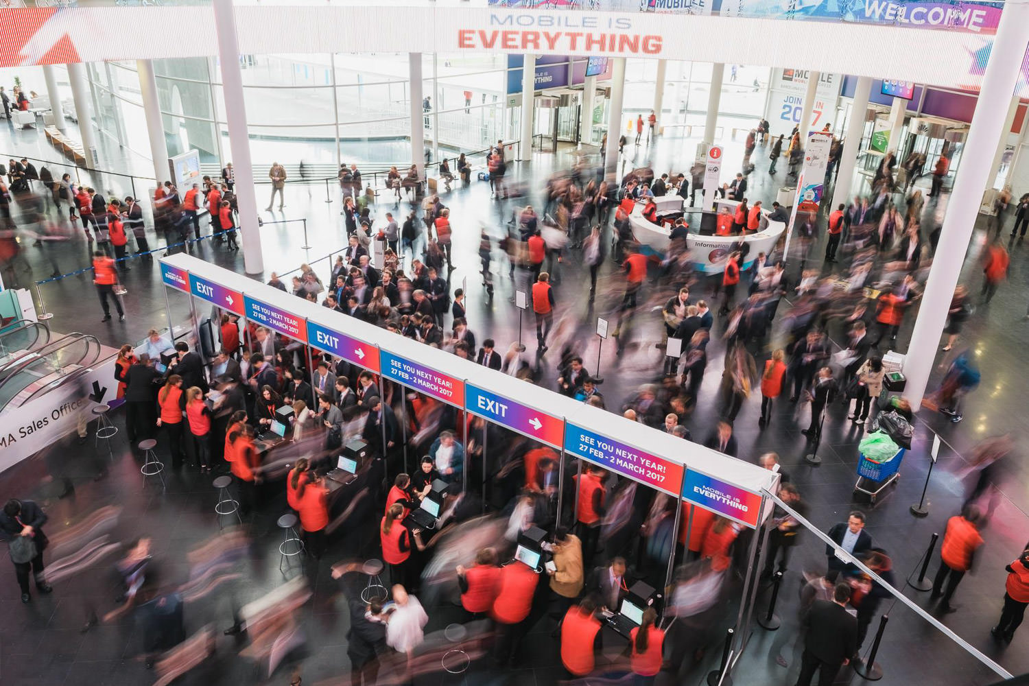 A long exposure photograph of people entering the Mobile World Conference event in Fira Barcelona, Spain.