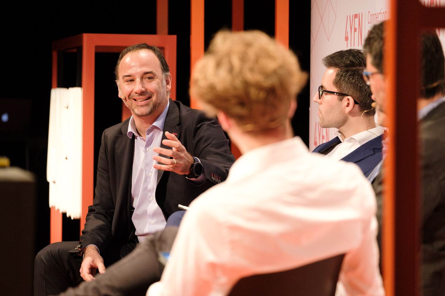 A photograph of Oscar Sala talking on stage, with Carles Puente, Josemaria Sota and Martin Dietz, on the AGORA stage during the 4YFN conference in Barcelona, Spain.