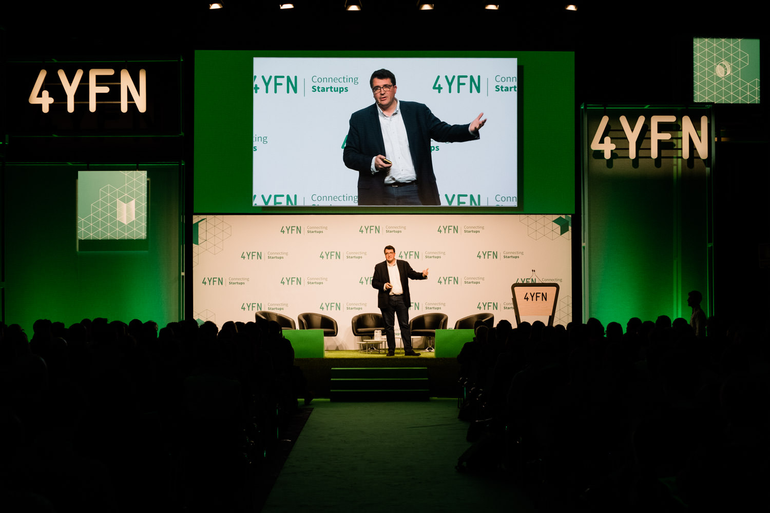 A photograph of a man speaking on stage during the 4YFN event in Barcelona, Spain